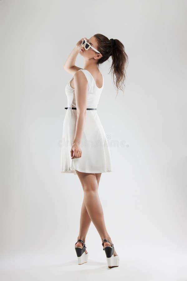 Πορτρέτο μόδας μιας γυναίκας ένα νέο όμορφο κορίτσι σε μια ελαφριά άσπρη τοποθέτηση φορεμάτων στο στούντιο Γυαλιά ηλίου στοκ εικόνα με δικαίωμα ελεύθερης χρήσης