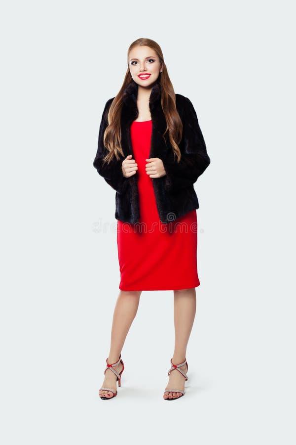 Πορτρέτο μόδας της αρκετά πρότυπης γυναίκας στο μαύρο παλτό και του κόκκινου φορέματος στο άσπρο υπόβαθρο στοκ φωτογραφία με δικαίωμα ελεύθερης χρήσης