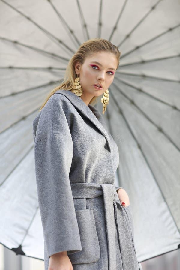 Πορτρέτο μόδας της νέας κομψής γυναίκας στο γκρίζο παλτό, τα μαύρα εσώρουχα, τις μαύρες μπότες αστραγάλων και τα χρυσά σκουλαρίκι στοκ εικόνα