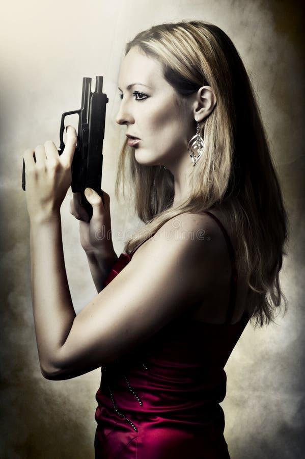 Πορτρέτο μόδας της προκλητικής γυναίκας με το πυροβόλο όπλο στοκ εικόνες