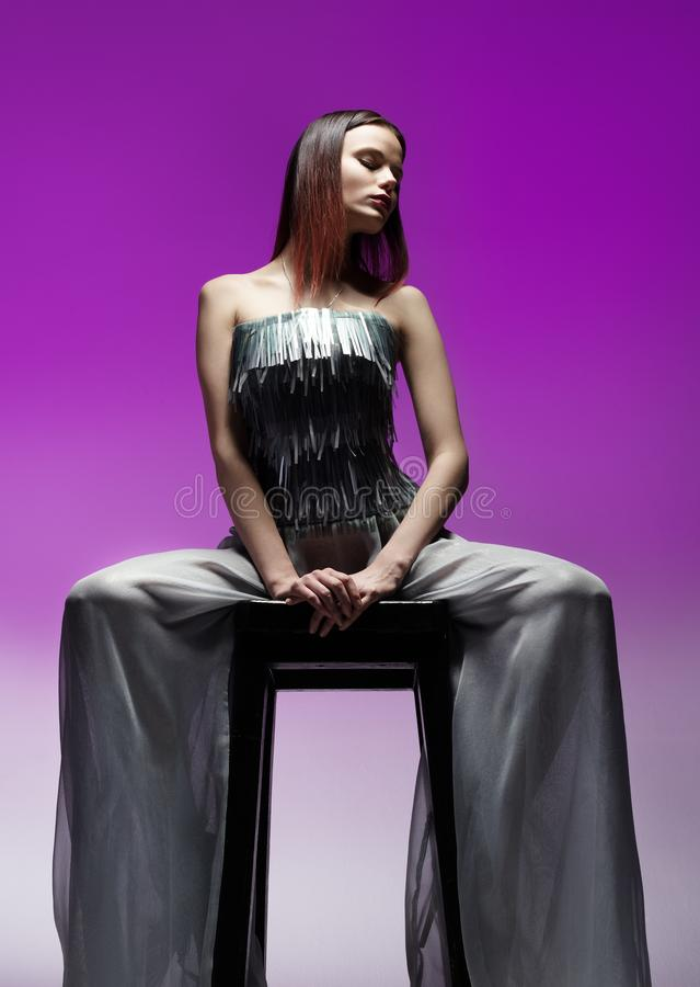 Πορτρέτο μόδας της όμορφης νέας συνεδρίασης γυναικών σε μια υψηλή καρέκλα στοκ φωτογραφία