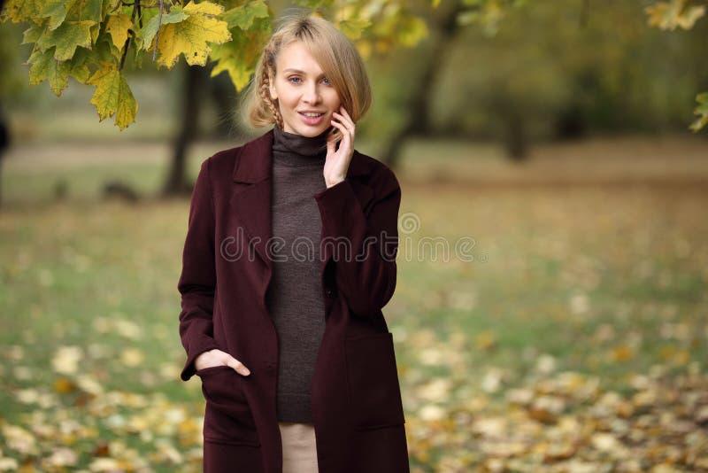 Πορτρέτο μόδας της όμορφης ξανθής γυναίκας στα μοντέρνα ενδύματα στο πάρκο φθινοπώρου στοκ φωτογραφίες
