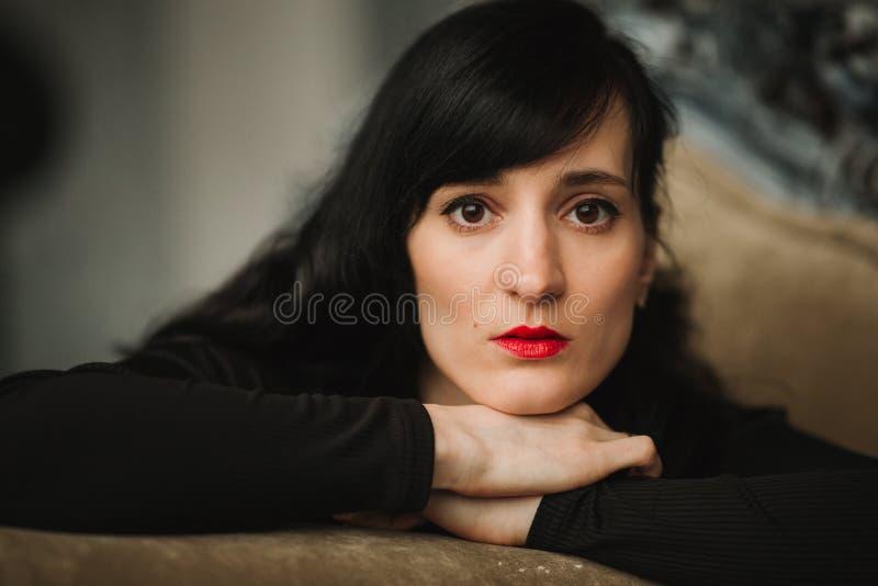 Πορτρέτο μόδας του νέου όμορφου θηλυκού προτύπου στη μαύρη προκλητική συνεδρίαση φορεμάτων στην καρέκλα βραχιόνων στο εσωτερικό σ στοκ εικόνες