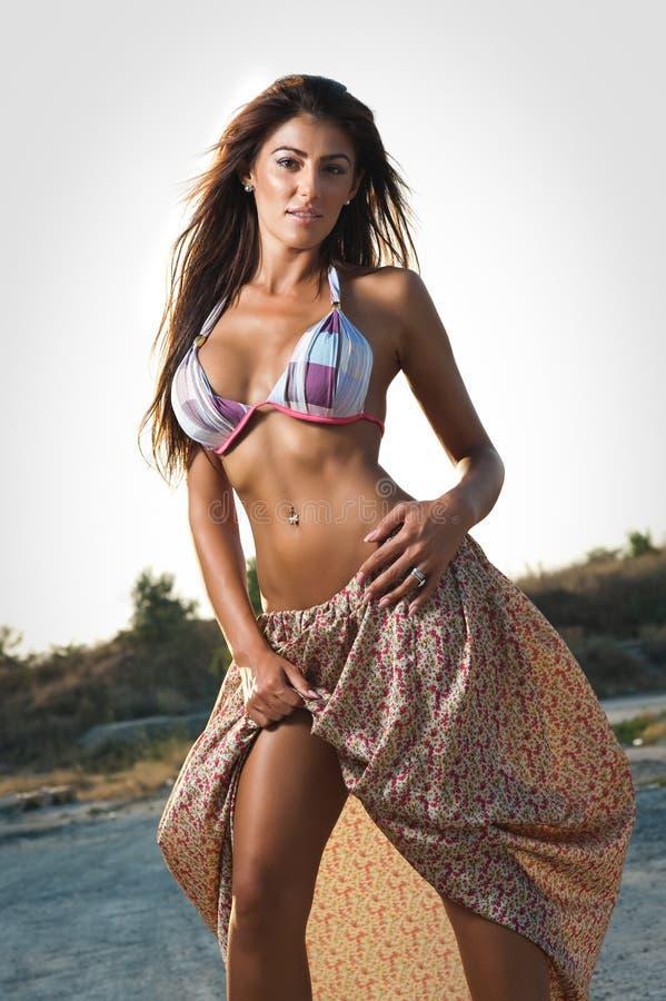 Πορτρέτο μόδας του προκλητικού κοριτσιού brunette στο μαγιό που κλίνει σε μια ξύλινη βάρκα Αισθησιακή ελκυστική γυναίκα με τη μακ στοκ εικόνες