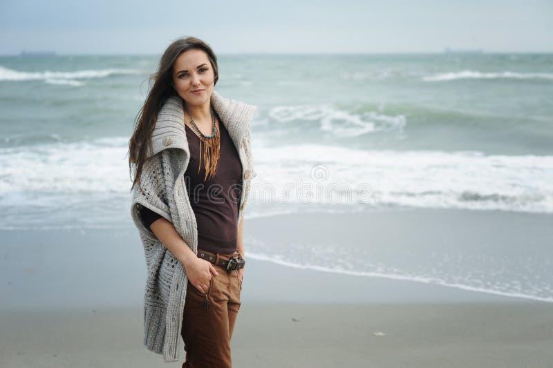 Πορτρέτο μόδας τρόπου ζωής φθινοπώρου του νέου μοντέρνου περπατήματος γυναικών hipster σε μια παραλία θάλασσας στοκ εικόνα με δικαίωμα ελεύθερης χρήσης