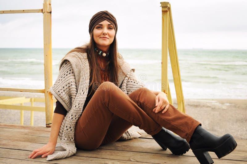 Πορτρέτο μόδας μιας όμορφης συνεδρίασης γυναικών brunette χαμόγελου μπροστά από την πόλης παραλία, χαμόγελο και εξέταση τη κάμερα στοκ φωτογραφία με δικαίωμα ελεύθερης χρήσης