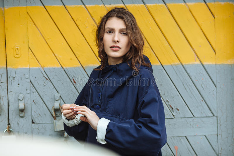Πορτρέτο μόδας της μοντέρνης όμορφης τοποθέτησης γυναικών ενάντια στην πόρτα αποθηκών εμπορευμάτων στη νεφελώδη ημέρα Φθορά της κ στοκ εικόνα