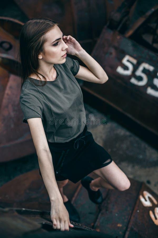 Πορτρέτο μόδας του μοντέρνου κοριτσιού στο μαύρο ύφος βράχου που στέκεται υπαίθρια στοκ εικόνες
