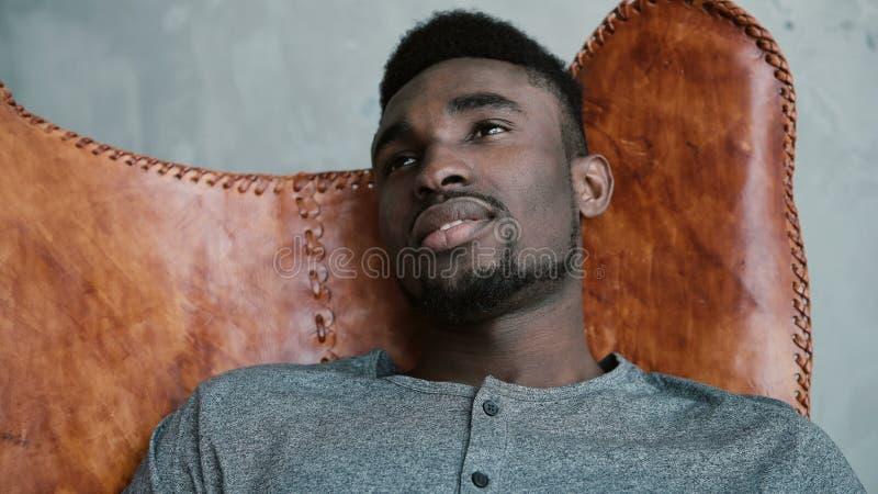 _πορτρέτο νέος αφρικανικός αρσενικός συνεδρίαση δέρμα καρέκλα, σκέφτομαι για κάτι και χαμογελώ Το άτομο κοιτάζει σκεπτικά στοκ εικόνες