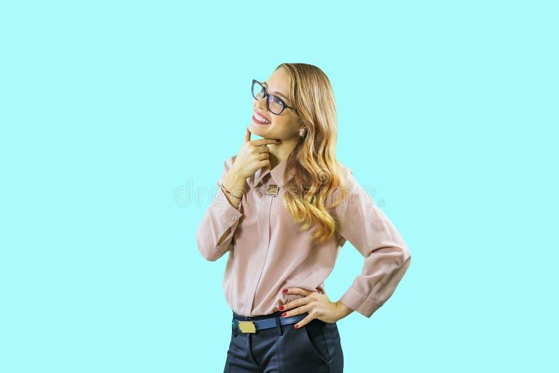 Πορτρέτο νέου σγουρού ενός ξανθού στα γυαλιά που φαίνεται σκεπτικά προς τα πάνω χαμογελώντας και κρατώντας δύο δάχτυλα κοντά στο  στοκ φωτογραφία με δικαίωμα ελεύθερης χρήσης
