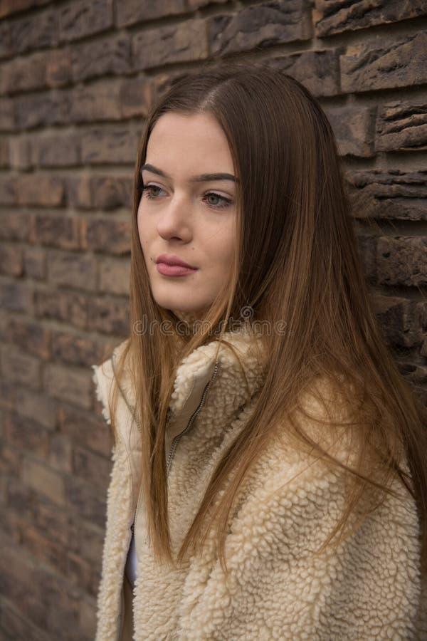 Πορτρέτο νέων κοριτσιών με το χειμερινό παλτό δίπλα στο τουβλότοιχο στοκ εικόνα