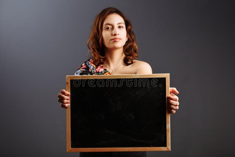 Πορτρέτο νεαρής Λατινοαμερικανίδας φοιτήτριας που κρατά ένα άδειο πίνακα με κιμωλία στο γκρι στοκ φωτογραφίες
