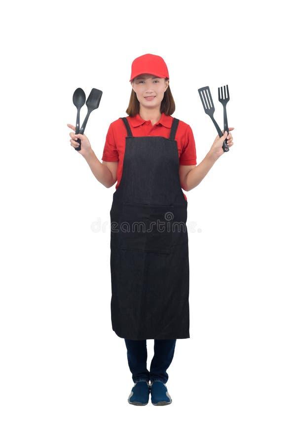 Πορτρέτο νεαρής οικονόμου που χαμογελάει με κόκκινη στολή και κρατά το χέρι της ποδιά Πλαστική κουταλιά απομονωμένη σε λευκό φόντ στοκ φωτογραφίες