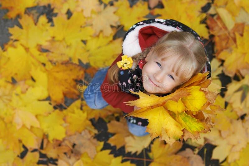 Πορτρέτο οδών φθινοπώρου του μικρού κοριτσιού που κρατά μια δέσμη των φύλλων σφενδάμου στοκ εικόνες