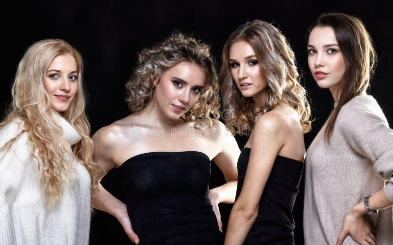 Πορτρέτο ομάδας τεσσάρων γυναικών στο μαύρο υπόβαθρο στοκ φωτογραφία