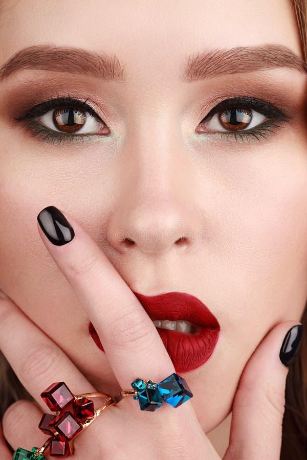 Πορτρέτο ομορφιάς κινηματογραφήσεων σε πρώτο πλάνο της νέας γυναίκας που φορά τα δαχτυλίδια με πράσινο, στοκ εικόνες