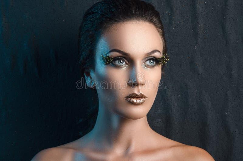 Πορτρέτο ομορφιάς μιας γυναίκας στο ύφασμα υποβάθρου, μπλε backlight στοκ εικόνες