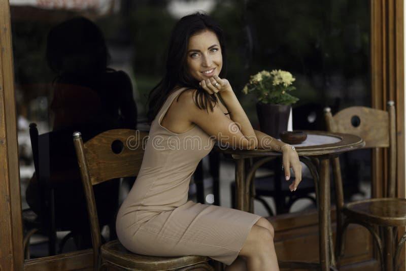 Πορτρέτο ομορφιάς μιας χαριτωμένης γυναίκας, παραμονές σε ένα τραπεζάκι σαλονιού στην παλαιά πόλη της Ελλάδας στοκ εικόνα
