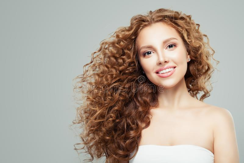 Πορτρέτο ομορφιάς μόδας της νέας redhead γυναίκας με το μακροχρόνιο υγιές σγουρό γκρίζο υπόβαθρο τρίχας στοκ φωτογραφία με δικαίωμα ελεύθερης χρήσης