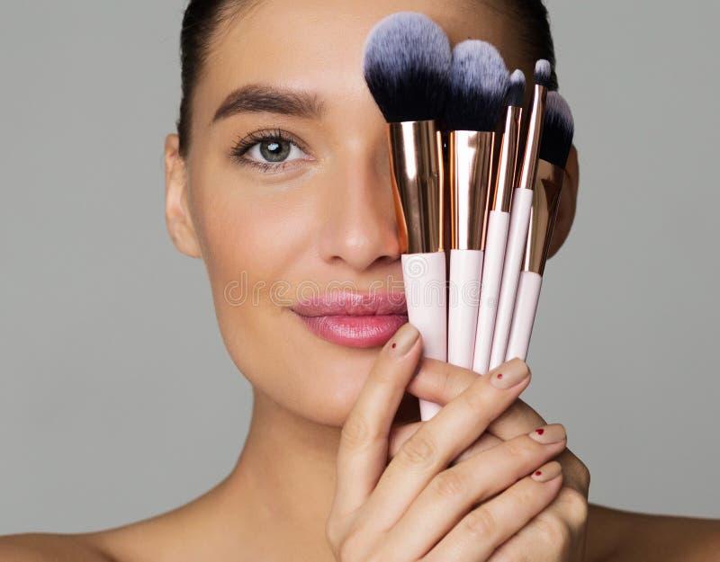 Πορτρέτο ομορφιάς της γυναίκας με τις βούρτσες Makeup κοντά στο πρόσωπο στοκ φωτογραφίες