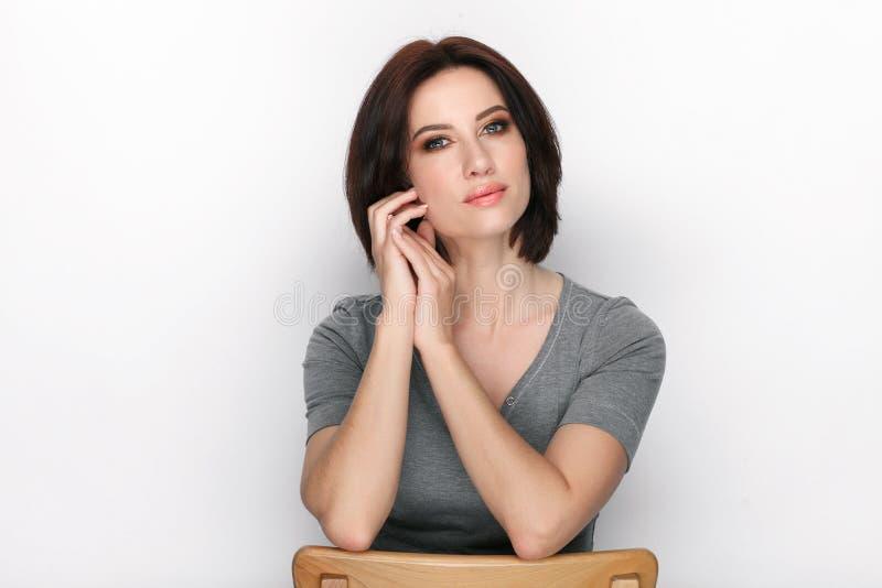 Πορτρέτο ομορφιάς της ενήλικης λατρευτής φρέσκιας κοιτάζοντας γυναίκας brunette με την τοποθέτηση hairdo βαριδιών στο άσπρο κλίμα στοκ εικόνα με δικαίωμα ελεύθερης χρήσης