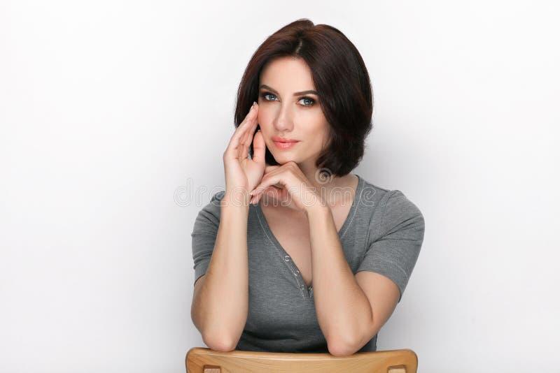 Πορτρέτο ομορφιάς της ενήλικης λατρευτής φρέσκιας κοιτάζοντας γυναίκας brunette με την τοποθέτηση hairdo βαριδιών στο άσπρο κλίμα στοκ εικόνα
