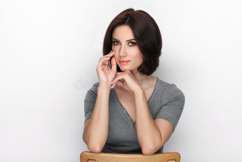 Πορτρέτο ομορφιάς της ενήλικης λατρευτής φρέσκιας κοιτάζοντας γυναίκας brunette με την τοποθέτηση hairdo βαριδιών στο άσπρο κλίμα στοκ φωτογραφία
