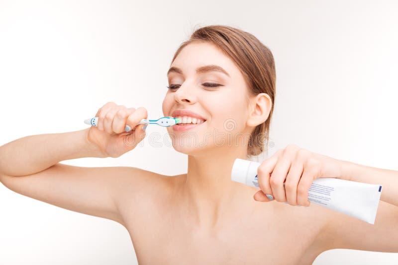 Πορτρέτο ομορφιάς της ευτυχούς νέας γυναίκας που βουρτσίζει τα δόντια της στοκ φωτογραφίες