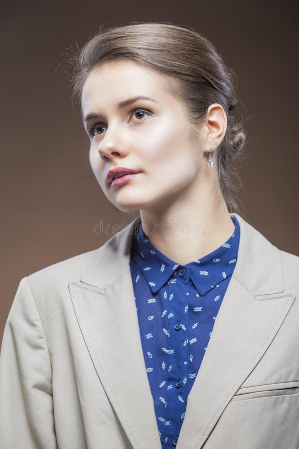 Πορτρέτο ομορφιάς του νέου καυκάσιου κοριτσιού στο χλωμό σακάκι και το μπλε πουκάμισο που κοιτάζει προς τα εμπρός στοκ φωτογραφία με δικαίωμα ελεύθερης χρήσης