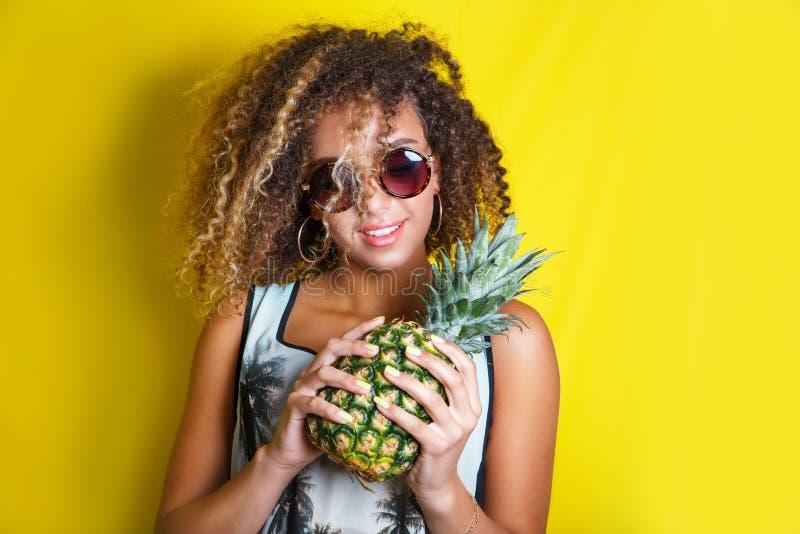 Πορτρέτο ομορφιάς του νέου κοριτσιού αφροαμερικάνων με το afro hairstyle στα γυαλιά ηλίου Τοποθέτηση κοριτσιών στο κίτρινο υπόβαθ στοκ εικόνες
