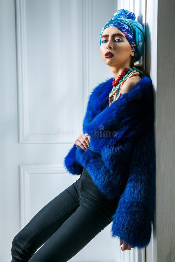 Πορτρέτο ομορφιάς του προτύπου μόδας με το χρωματισμένα headwear, μπλε φρύδι και τα χείλια παλτών γουνών κόκκινα makeup και το πε στοκ εικόνες με δικαίωμα ελεύθερης χρήσης