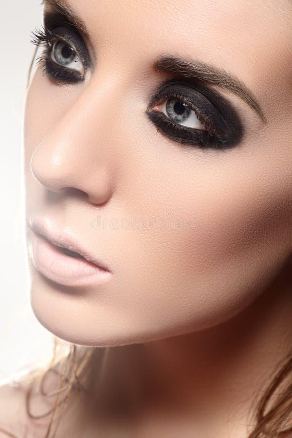 Πορτρέτο ομορφιάς του πρότυπου προσώπου με τη σκοτεινή σύνθεση καπνώδης-ματιών μόδας στοκ εικόνα