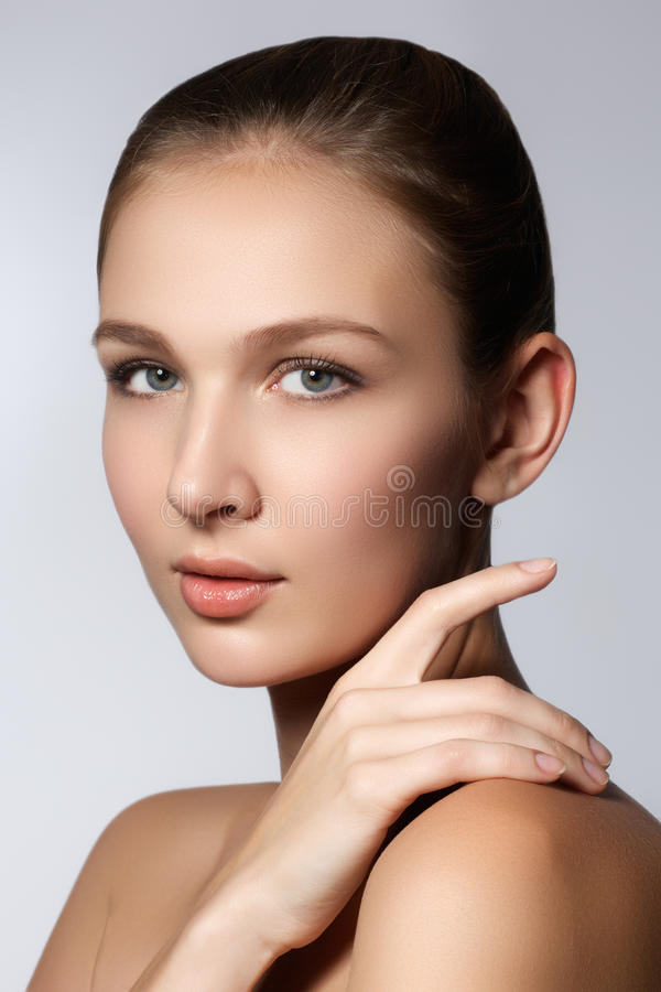 Πορτρέτο ομορφιάς Beautiful Spa γυναίκα σχετικά με το πρόσωπό της Τέλειο φρέσκο δέρμα E Νεολαία και έννοια φροντίδας δέρματος στοκ εικόνα