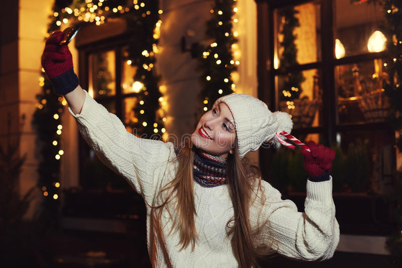 Πορτρέτο οδών νύχτας μιας χαμογελώντας όμορφης νέας γυναίκας που κάνει selfie τη φωτογραφία με το smartphone της Εορταστικά Χριστ στοκ εικόνα