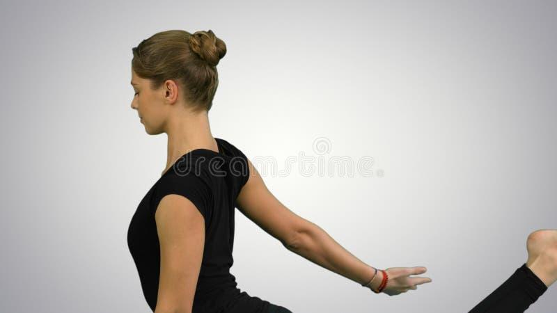 Πορτρέτο πλάγιας όψης της όμορφης νέας γυναίκας που κάνει τη γιόγκα ή pilates την άσκηση Ένα με πόδια περιστέρι βασιλιάδων θέτει, στοκ εικόνες