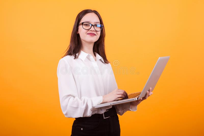 Πορτρέτο πλάγιας όψης του όμορφου κοριτσιού που κρατά το φορητό υπολογιστή στο στούντιο πέρα από το κίτρινο υπόβαθρο στοκ φωτογραφία με δικαίωμα ελεύθερης χρήσης