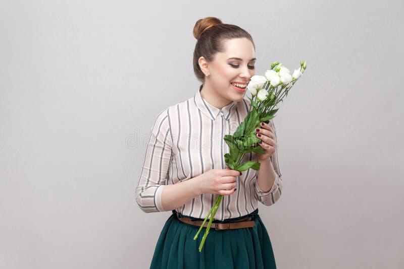 Πορτρέτο πλάγιας όψης του όμορφου όμορφου χαμογελώντας κοριτσιού γυναικών ευχαρίστησης ρομαντικού νέου στη ριγωτή ανθοδέσμη εκμετ στοκ εικόνα