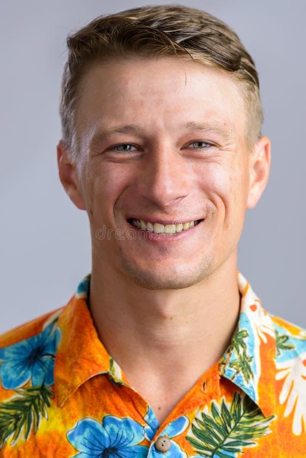 Πορτρέτο που πυροβολείται του νέου ευτυχούς καυκάσιου ατόμου στο της Χαβάης πουκάμισο ISO στοκ εικόνα