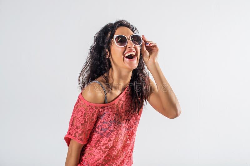 Πορτρέτο στούντιο ενός εύθυμου κοριτσιού που έχει τη διασκέδαση, φορώντας τα γυαλιά ηλίου και την καθιερώνουσα τη μόδα θερινή εξά στοκ εικόνες