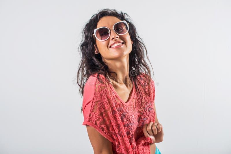 Πορτρέτο στούντιο ενός εύθυμου κοριτσιού που έχει τη διασκέδαση, φορώντας τα γυαλιά ηλίου και την καθιερώνουσα τη μόδα θερινή εξά στοκ φωτογραφία με δικαίωμα ελεύθερης χρήσης