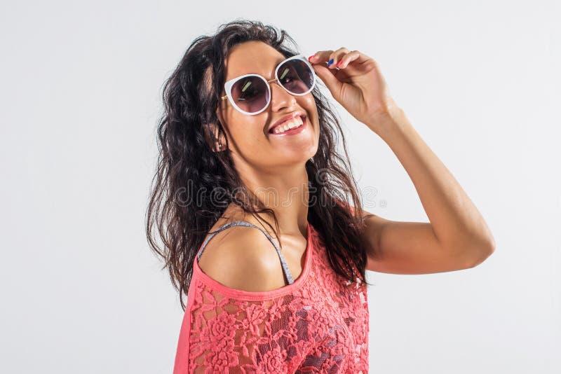 Πορτρέτο στούντιο ενός εύθυμου κοριτσιού που έχει τη διασκέδαση, φορώντας τα γυαλιά ηλίου και την καθιερώνουσα τη μόδα θερινή εξά στοκ φωτογραφία