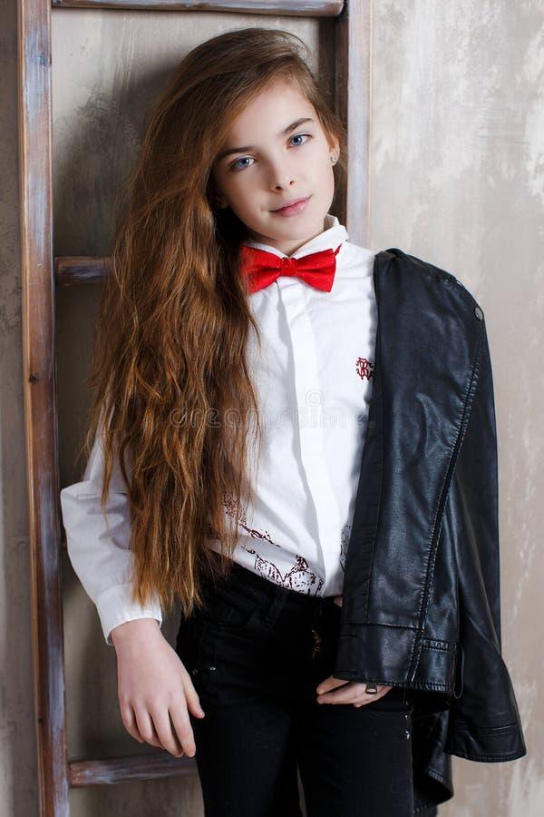 Πορτρέτο στούντιο ενός κοριτσιού σε ένα άσπρο πουκάμισο με έναν δεσμό τόξων σε ένα γκρίζο υπόβαθρο στοκ φωτογραφίες