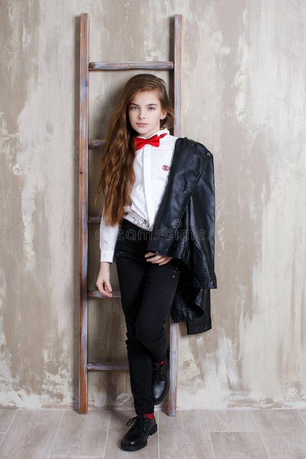 Πορτρέτο στούντιο ενός κοριτσιού σε ένα άσπρο πουκάμισο με έναν δεσμό τόξων σε ένα γκρίζο υπόβαθρο στοκ εικόνες