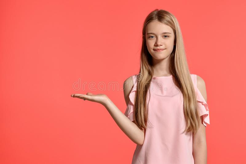 Πορτρέτο στούντιο ενός όμορφου ξανθού εφήβου κοριτσιών σε μια ροδοειδή τοποθέτηση μπλουζών στο ρόδινο υπόβαθρο στοκ εικόνες με δικαίωμα ελεύθερης χρήσης