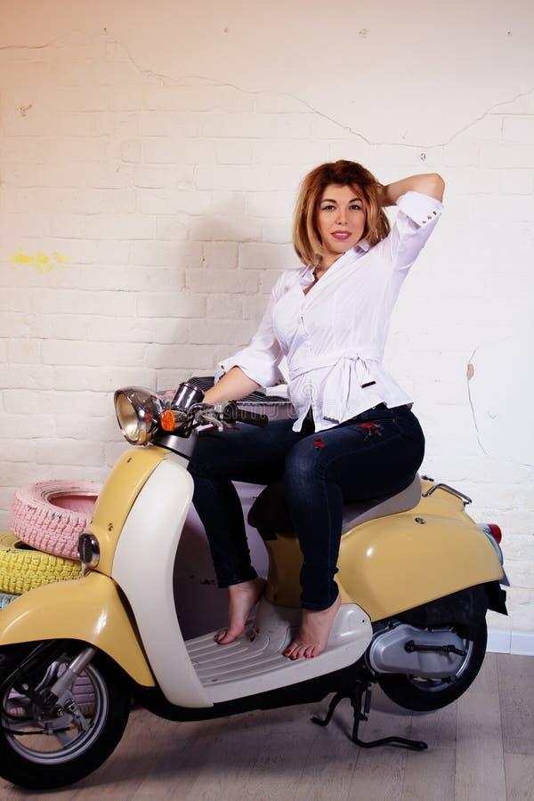 Πορτρέτο στούντιο μιας ευτυχούς καυκάσιας συνεδρίασης γυναικών στο μηχανικό δίκυκλο barefeet στοκ φωτογραφίες