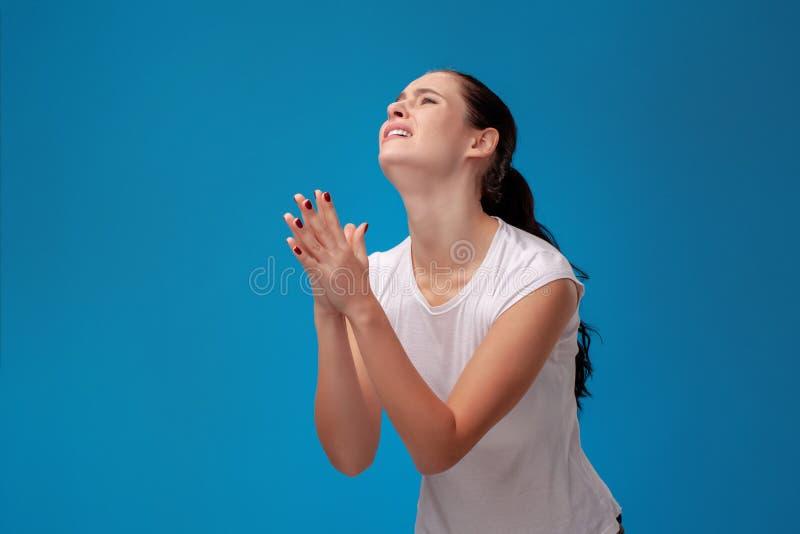 Πορτρέτο στούντιο μιας νέας όμορφης γυναίκας σε μια άσπρη μπλούζα σε ένα μπλε κλίμα τοίχων Ειλικρινείς συγκινήσεις ανθρώπων στοκ εικόνες