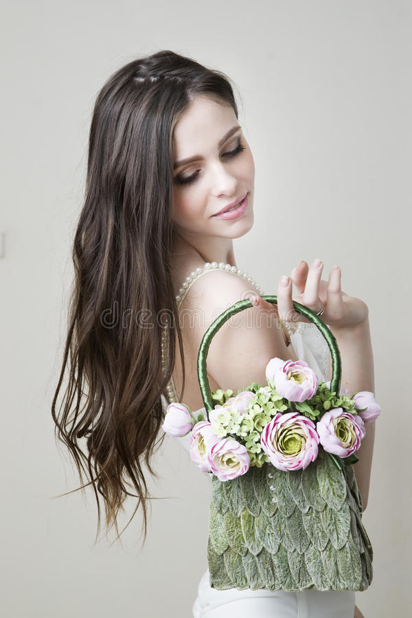 Πορτρέτο στούντιο μιας νέας όμορφης νύφης με την τσάντα της στο χέρι της στοκ εικόνες