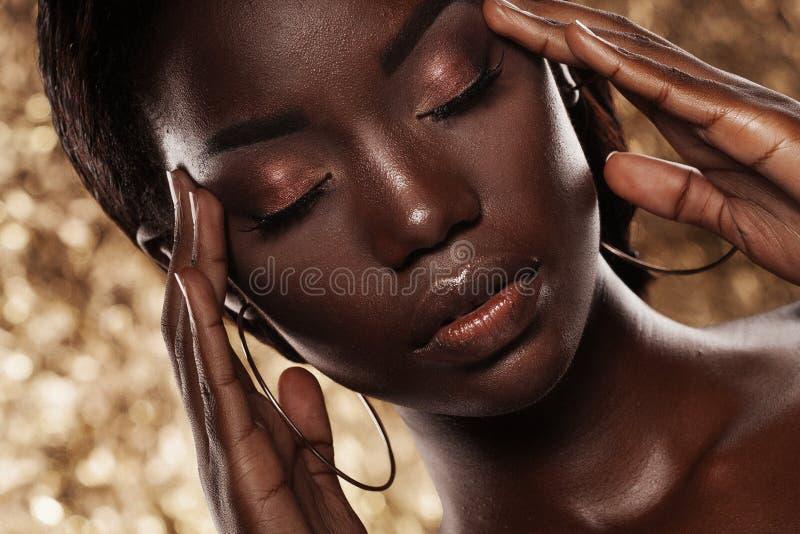 Πορτρέτο στούντιο μόδας ενός εξαιρετικού όμορφου προτύπου αφροαμερικάνων με τις ιδιαίτερες προσοχές πέρα από το χρυσό υπόβαθρο στοκ εικόνες