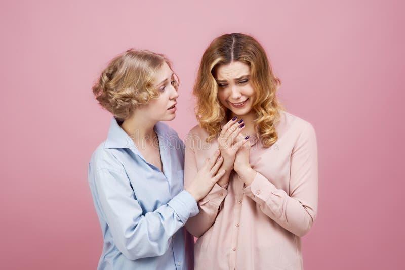 Πορτρέτο στούντιο στο ρόδινο υπόβαθρο δύο νέων κοριτσιών Ένας φίλος που ανακουφίζει ένα φωνάζοντας κορίτσι και εξηγεί ότι όλοι θα στοκ εικόνες