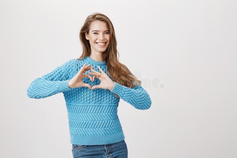 Πορτρέτο στούντιο της συγκινητικής καλής φίλης που παρουσιάζει χειρονομία καρδιών και που χαμογελά ευρέως εκφράζοντας τη στάση τη στοκ φωτογραφίες με δικαίωμα ελεύθερης χρήσης